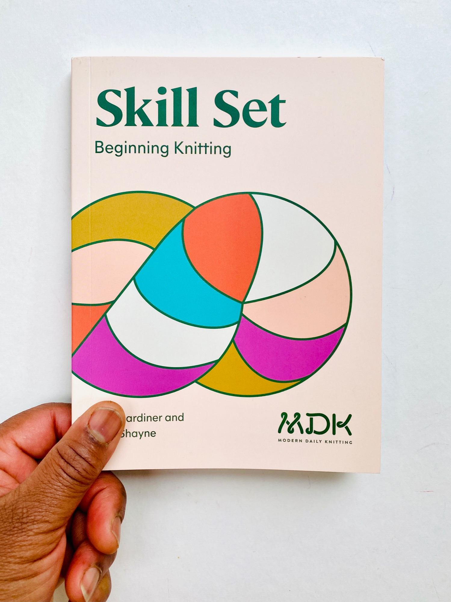 image of a black woman's left hand holding a print copy of Shill Set Beginner `Knitting by Modern  Daily Knitting