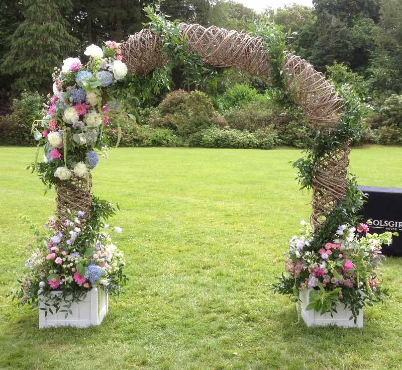 wicker wedding arch with summer flowers
