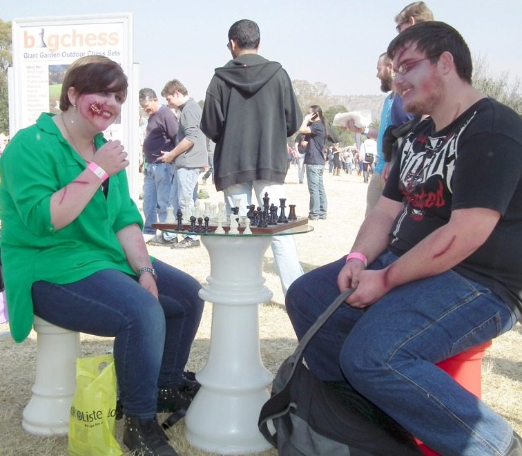"""A smiling couple playing """"small"""" chess at the queen table and sitting on castles."""