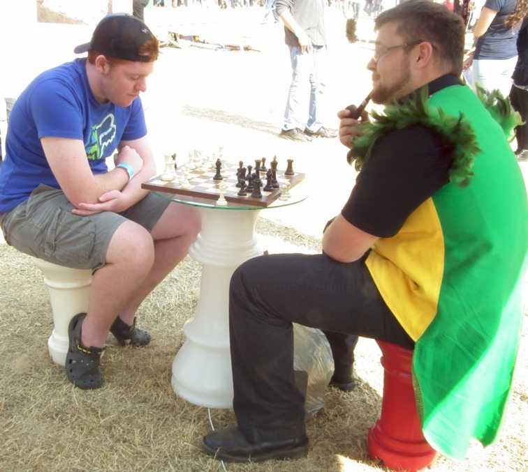 """A pipe smoker playing a game of """"small"""" chess."""