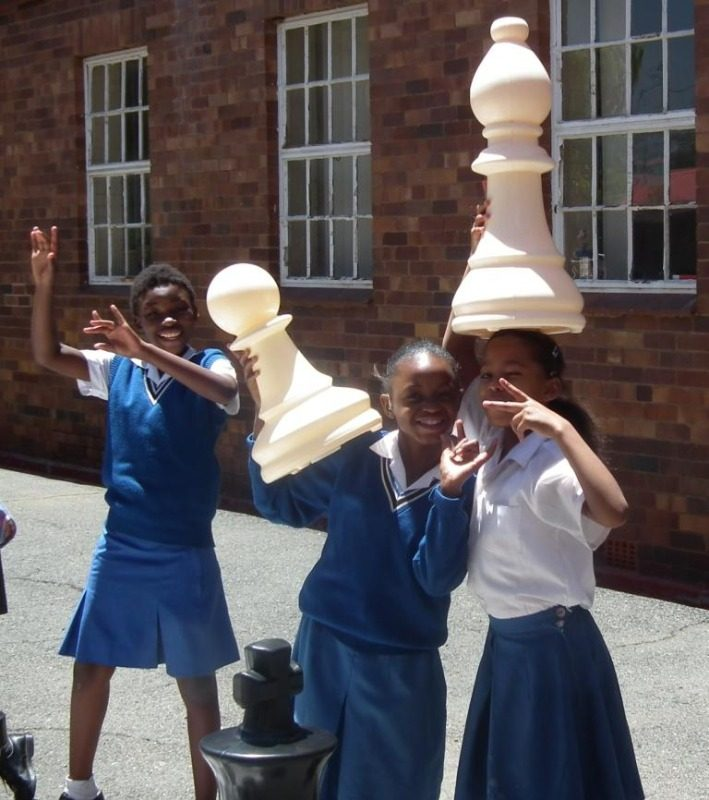 happy girls and chess pieces