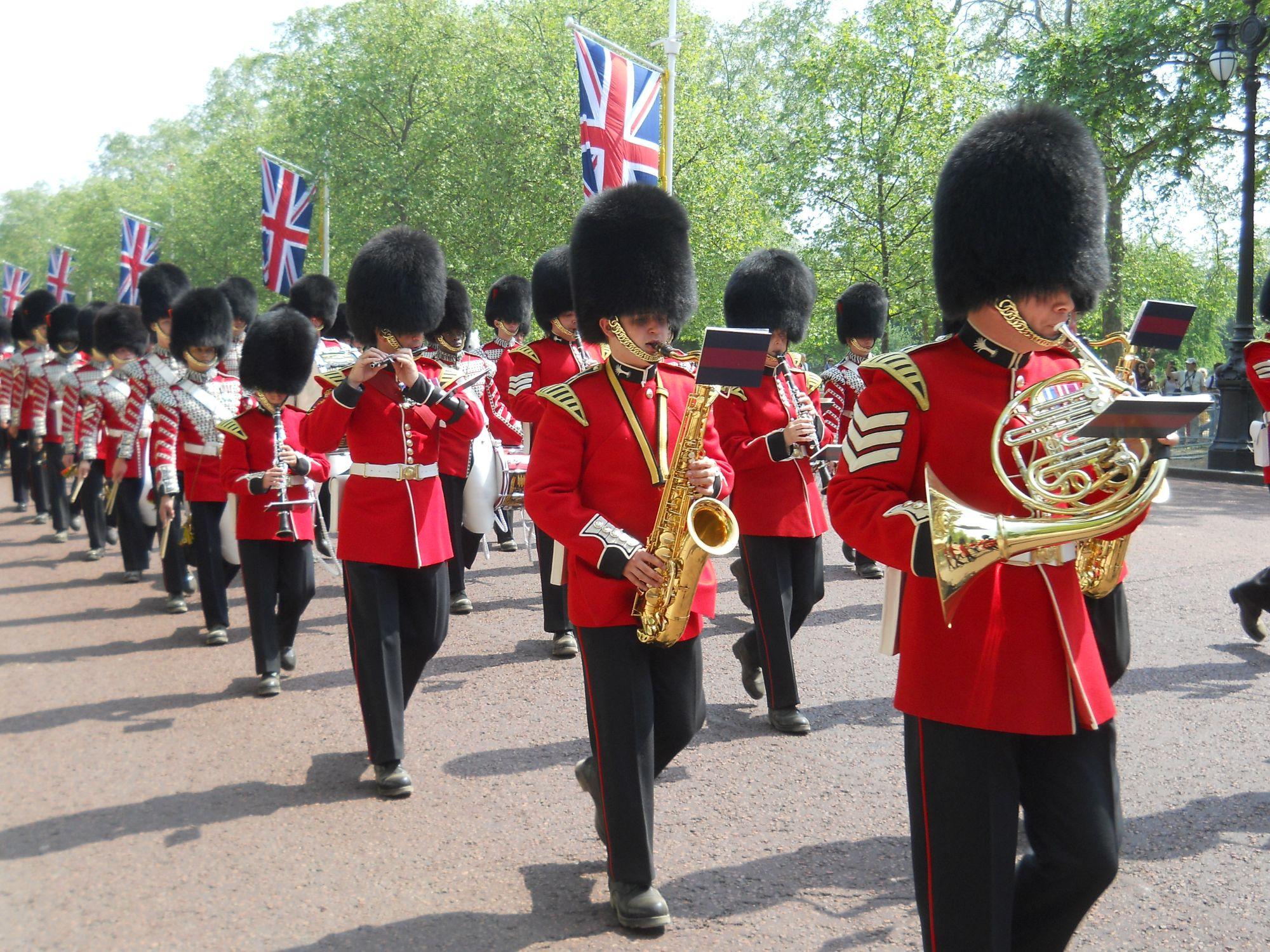 Photo of a military band marching  along The Mall. The soliders were scarlet jackets and black busbys. They are playing a selection of brass and woodwind instruments.