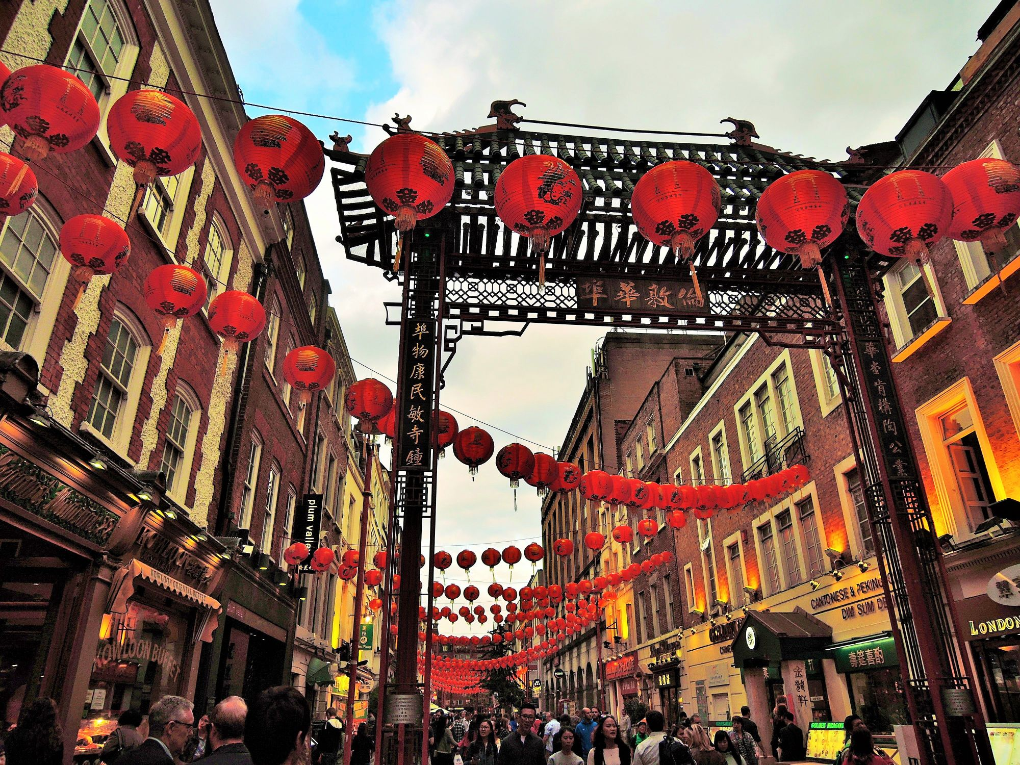 Photo of the main street in Chinatown. In the forefront is one of the ceremonial entrance gates. The street view shows restaurants and shops and the street is decorated with colourful, red paper lanterns.