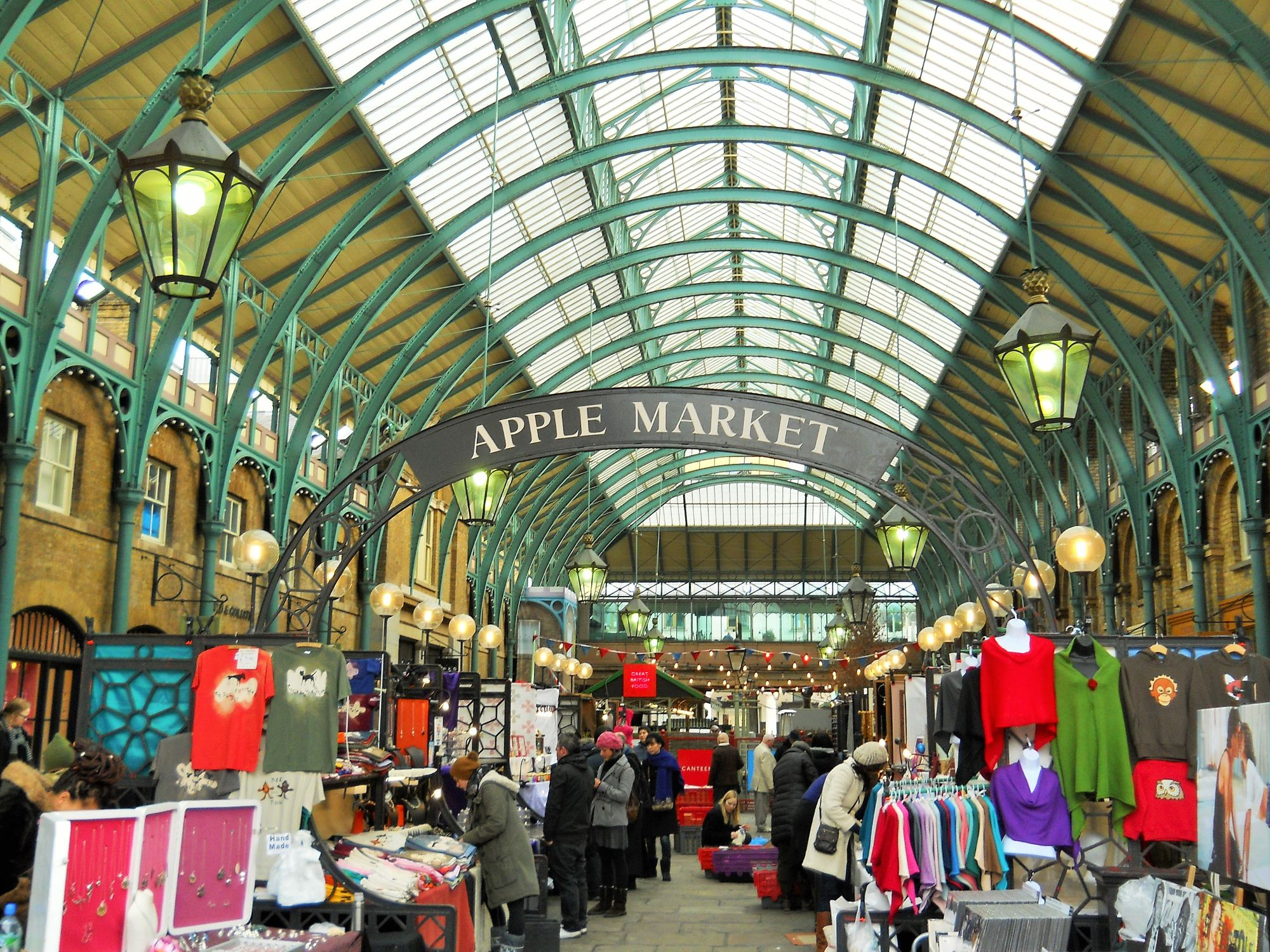 Photo of the indoor craft market at Covent Garden. Stalls selling a selection of clothes and gifts.