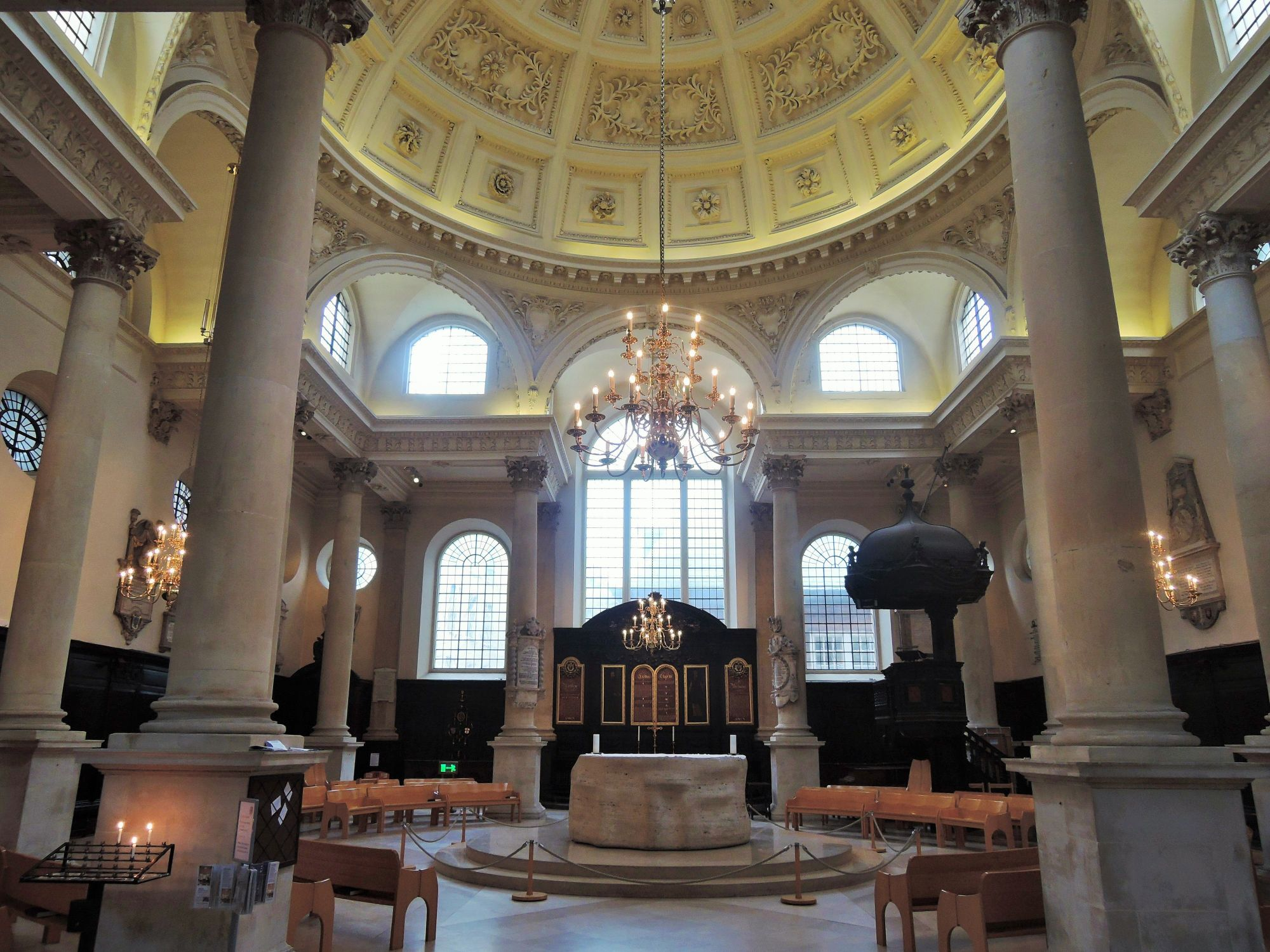 Photo of the interior of St Stephen's Walbrook. The contemporary altar has been described as looking like a piece of  camembert cheese. The stalls are laid out in a circle. There are several columns that support a domed roof.