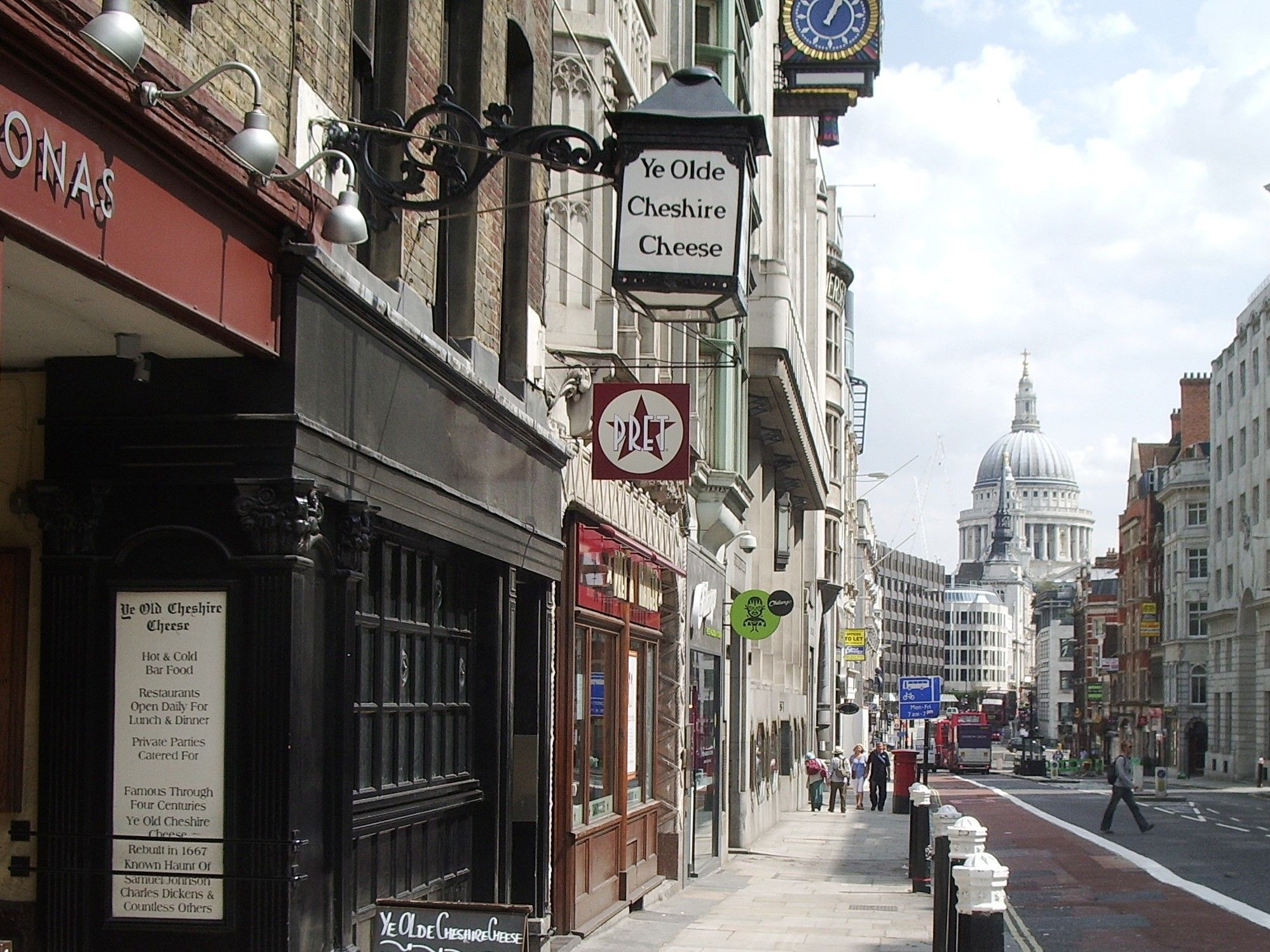 Photo of a street view of Fleet Street. In the foreground is Ye Old Cheshire Cheese, a historic pub with an old fashioned, overhanging lamp. The view looks down the road towards St Paul's Cathedral.