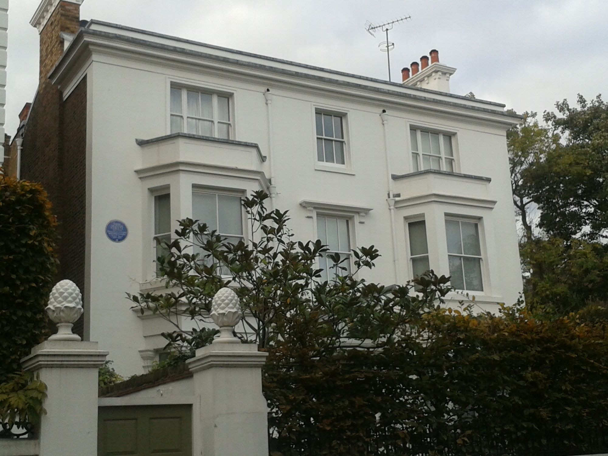 Photo of one of Agatha Christie's former London homes. A large detached house. There is a Blue Plaque commemorating Agatha on the left handside, next to a large bay window. The house is double fronted with and painted white. In the foreground is the front garden, with shrubs and plants.