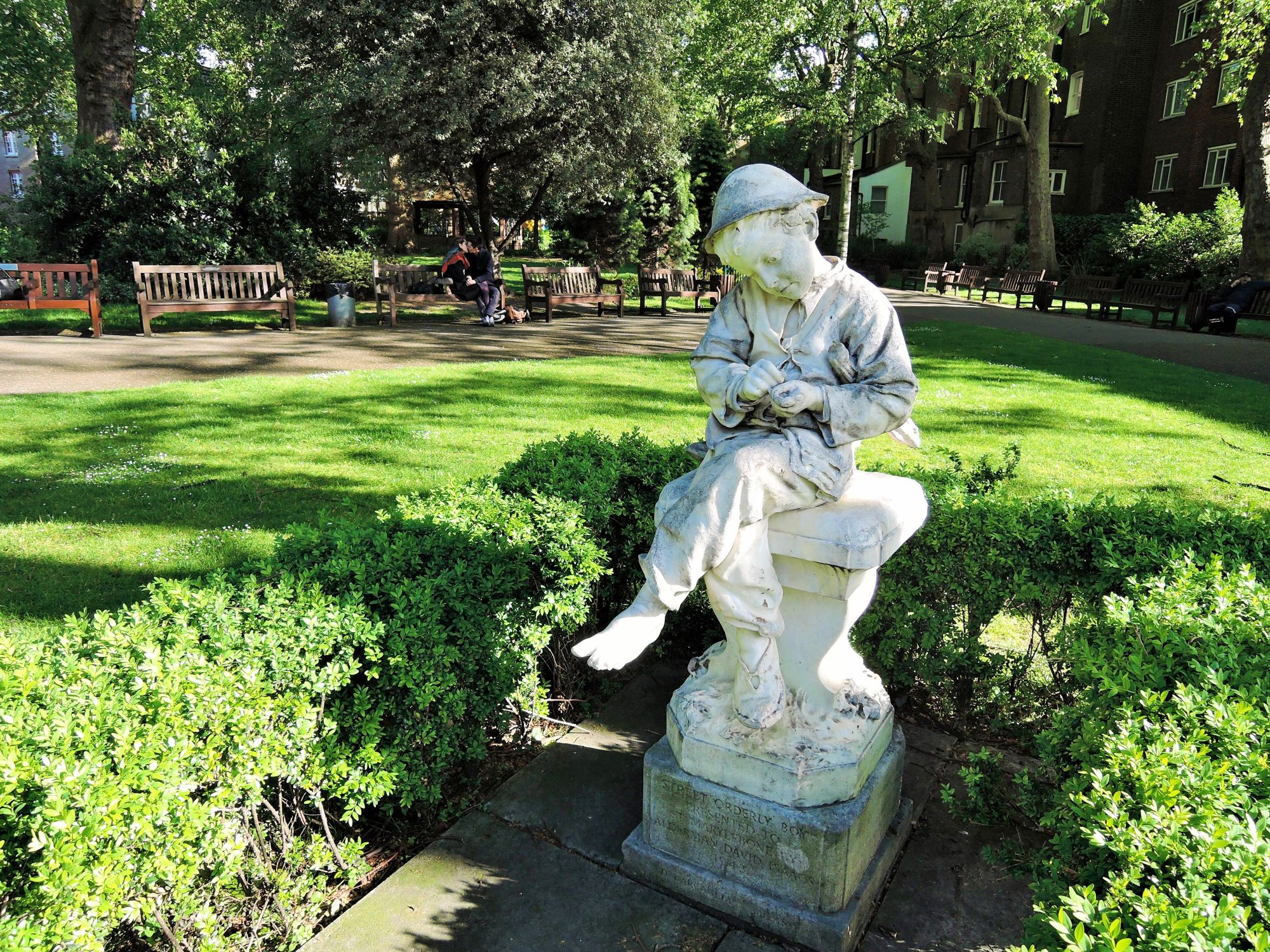 Photo of Paddington Street Gardens. In the foreground is a statue of a small boy in ragged clothing. In the background is a lawn, paths, benches, shrubs and trees.