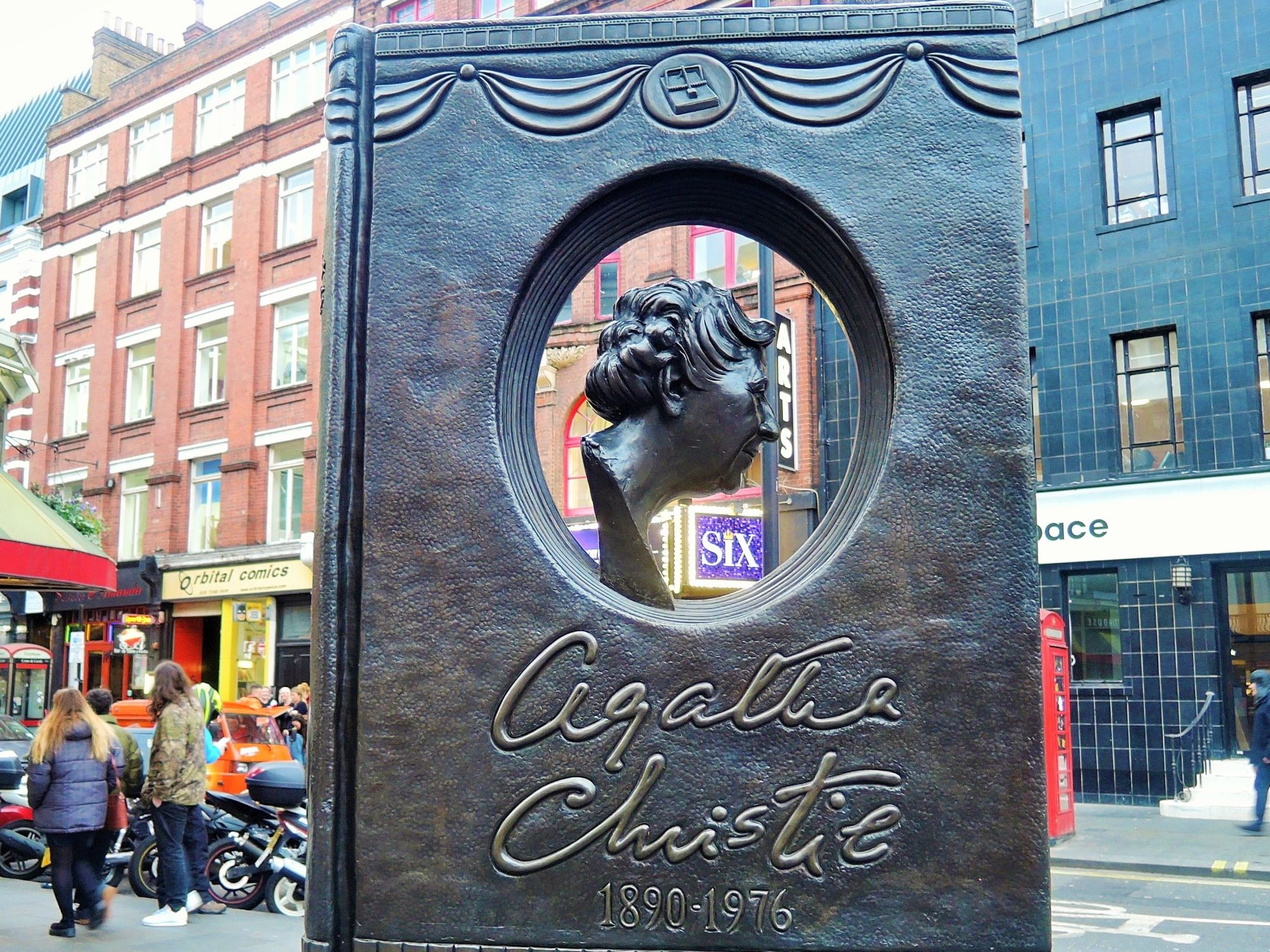 Photo of the Agatha Christie memorial. The sculpture resembles a closed book with an oval opening in the centre, in which there is a bust of Agatha Christie.