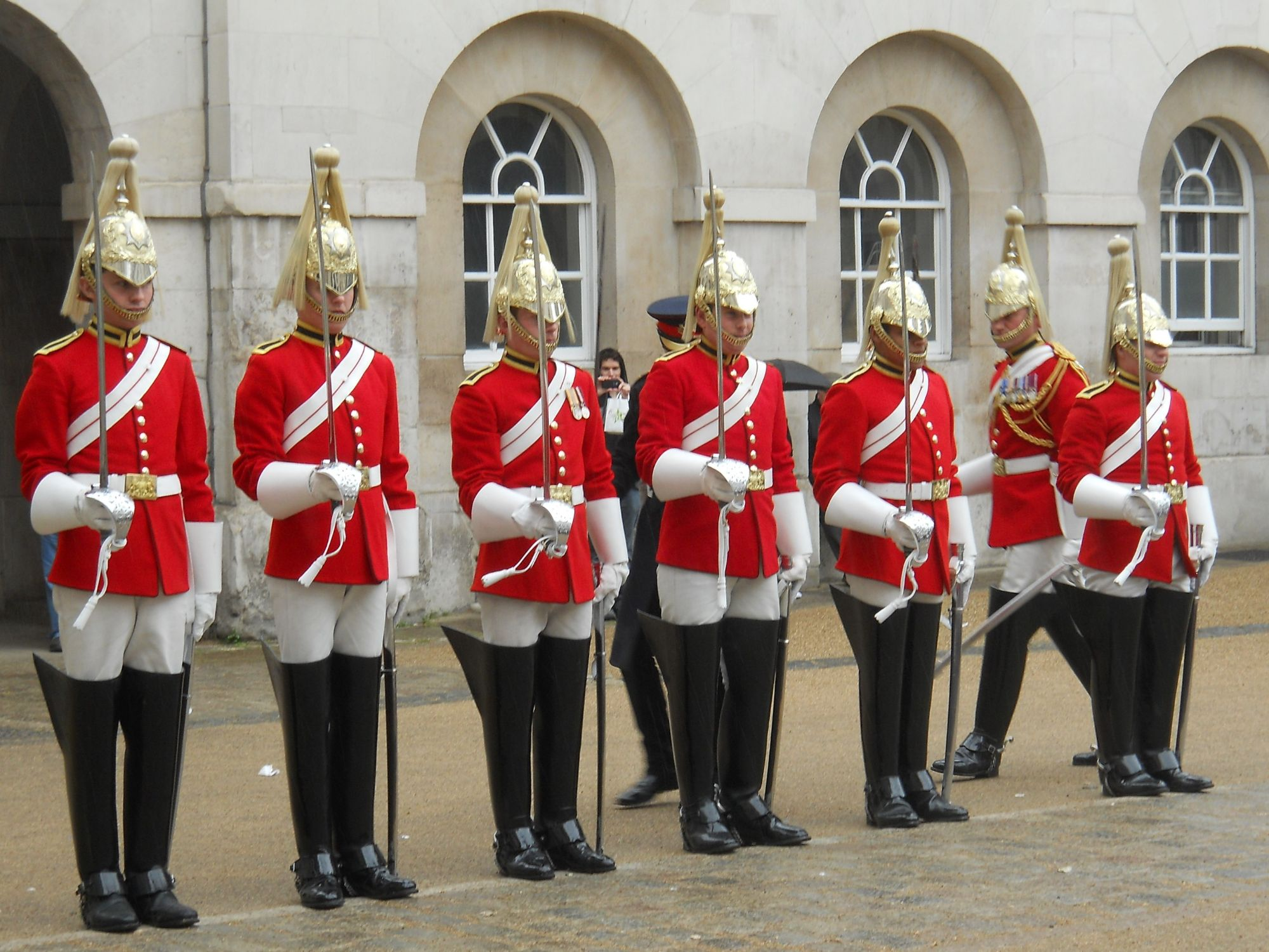 Photo of the Dismounting Ceremony in Horse Guards. Six soliders from the Life Guards regiment are standing on parade. They wear scarlet jackets, white trousers, long black boots and a helmet with a white ploom. They are each holding a sword. In the background two officers are inspecting them.