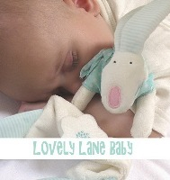 A contented baby with a Rufus Rabbit comforter from Lovely Lane Gifts