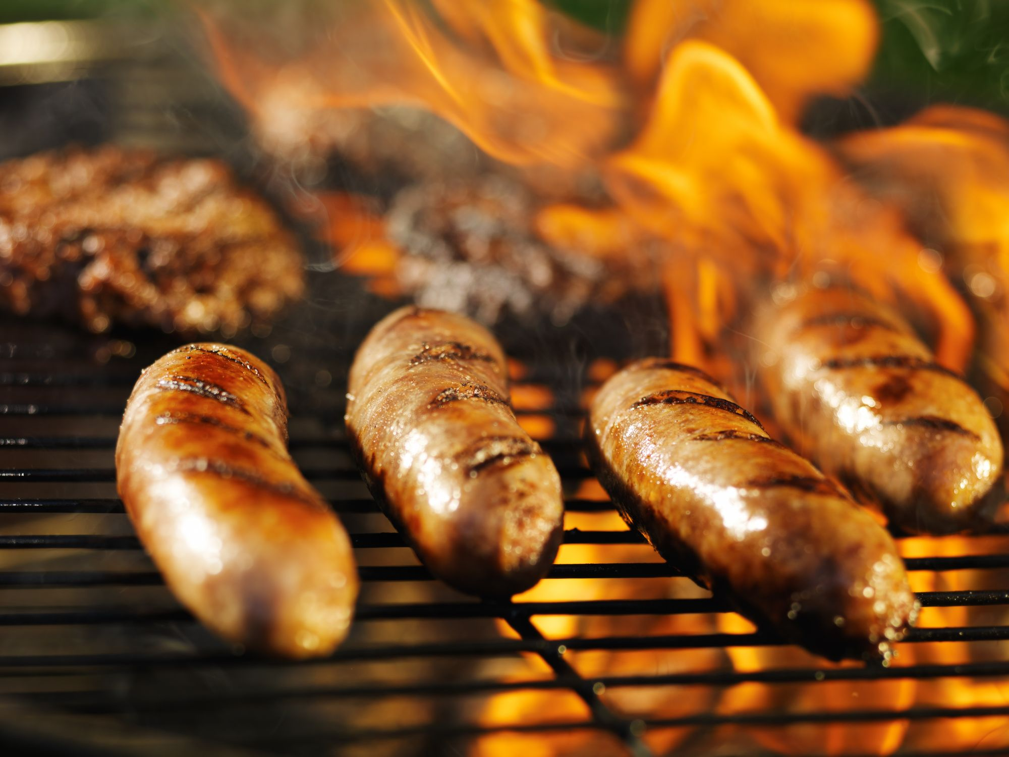 bratwursts-cooking-over-fire-on-barbecue-grill-515628317_7216x5412