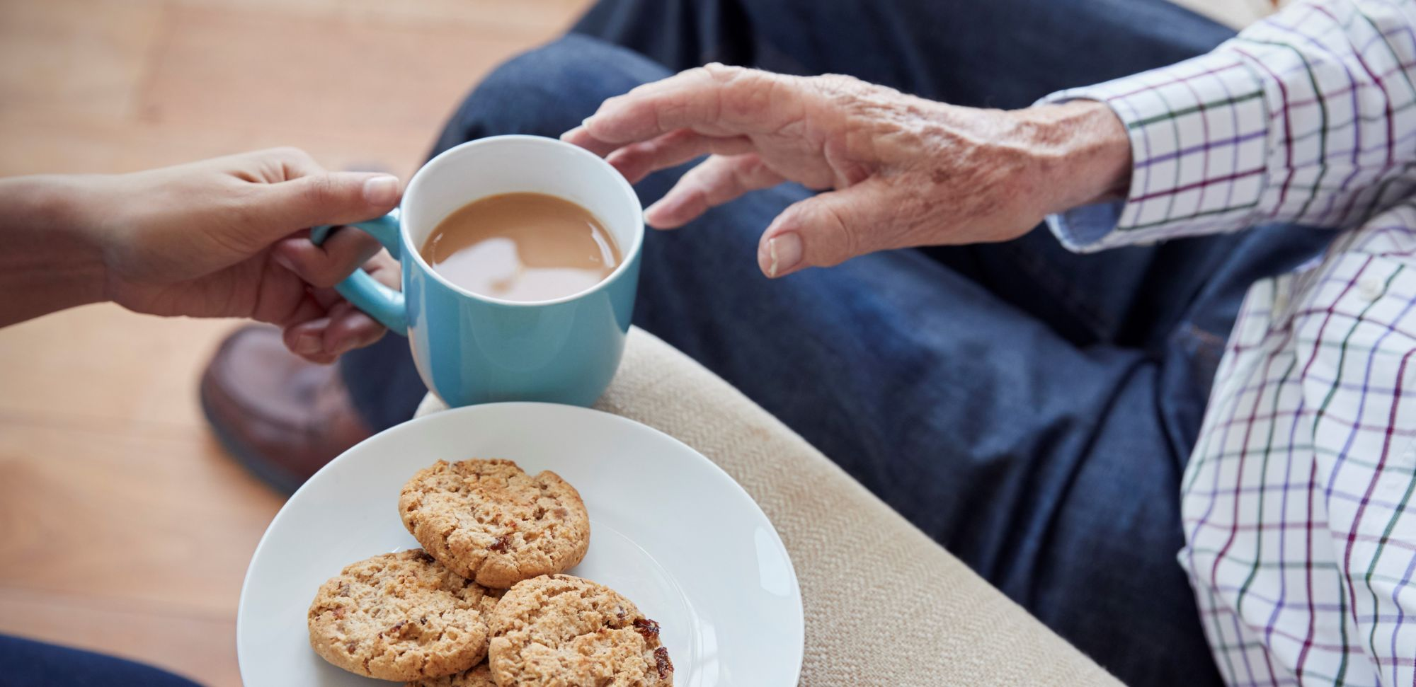 Woman-passes-tea-and-biscuits-to-a-seated-senior-man,-detail-849180252_4719x3147 CROP.jpeg