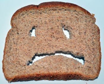 A-slice-of-bread-with-a-face-cut-into-it.-872243622_1144x920