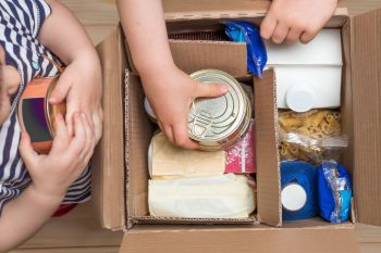 Children-opening-a-food-delivery-box-at-home,-online-ordering.-Grocery-stor