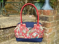 Red tapestry fabric handbag with leather handles