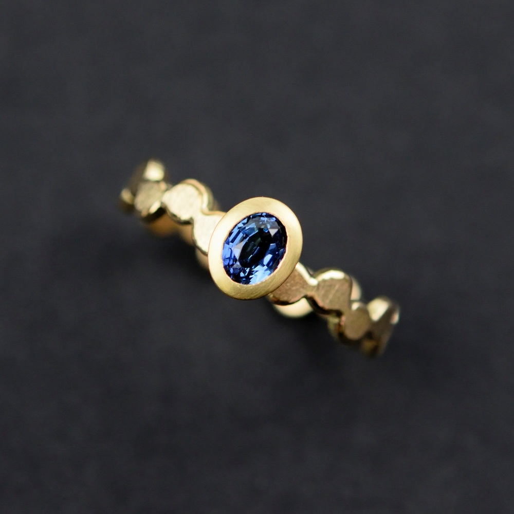 Simple pattern gold ring with blue oval sapphire