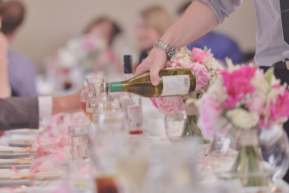 Man Pouring Wine At Wedding Restaurant Table