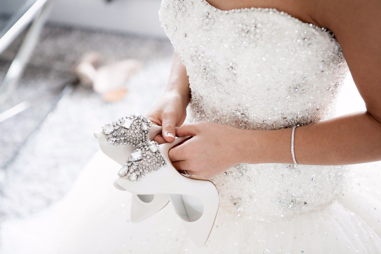 Bride holing shoes and wearing wedding dress