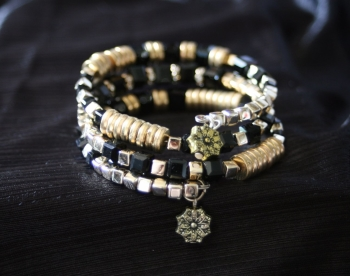Black and gold self winding bracelet with charm
