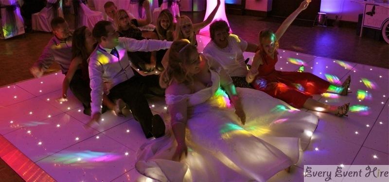 Wedding Party Sitting on Starlit Dance Floor