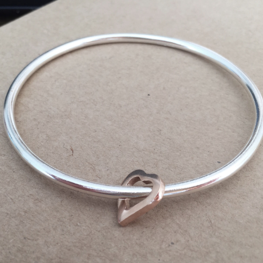 Silver bangle with rose gold heart. Round polished bangle with 9ct Rose Gol