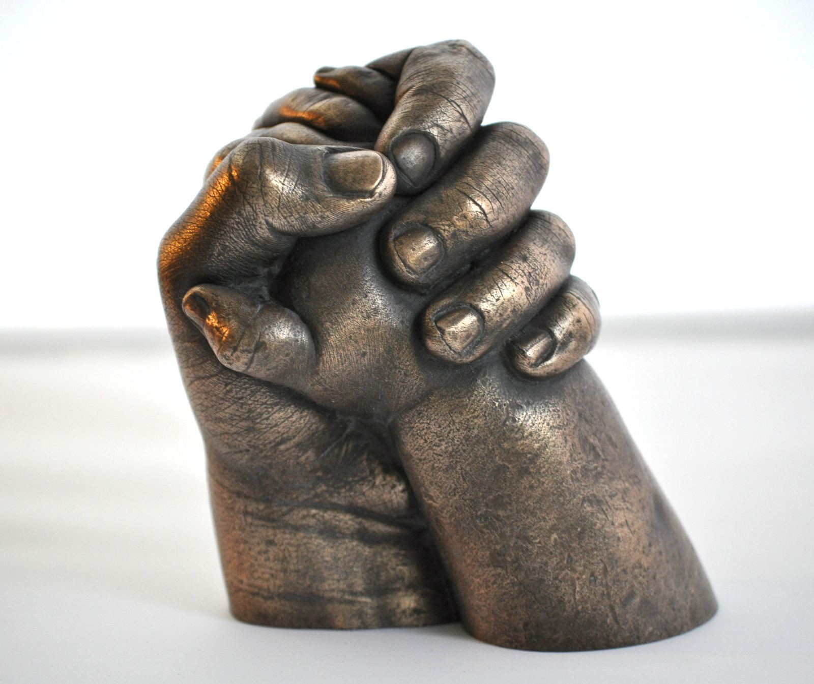 Sibling holding hands in bronze resin