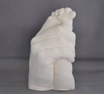 Father and baby holding hands in plaster