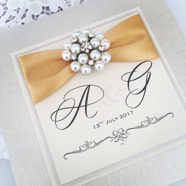Luxury handmade wedding invitations with brooches and ribbons