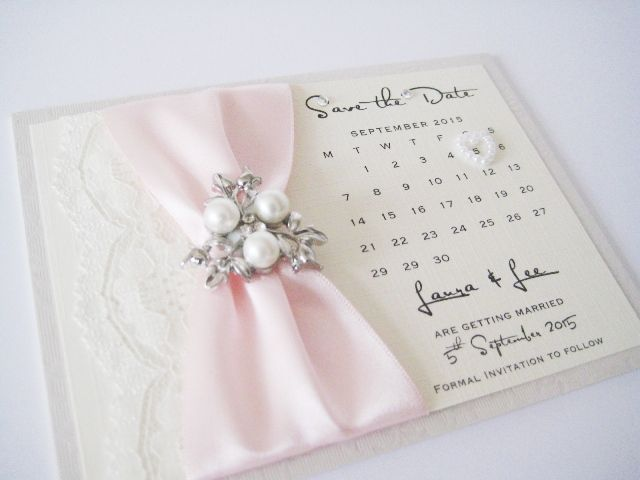 A vintage save the date card with ivory lace and pearl brooch