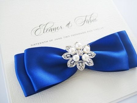 pocket style invitation with royal blue ribbon and pearl brooch