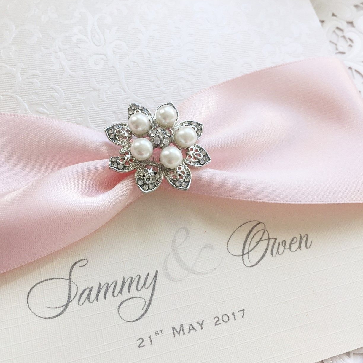 Vintage themed wedding invitation with pearl brooch