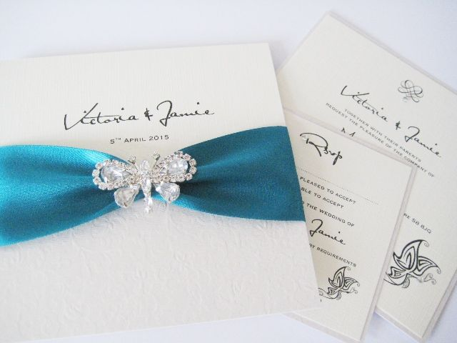 Teal invitations with butterfly brooch