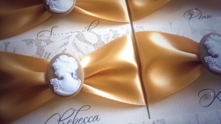 Cameo place name cards with gold ribbon