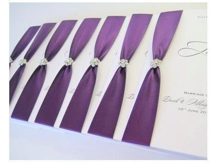 Order of service booklets with purple ribbon and diamante