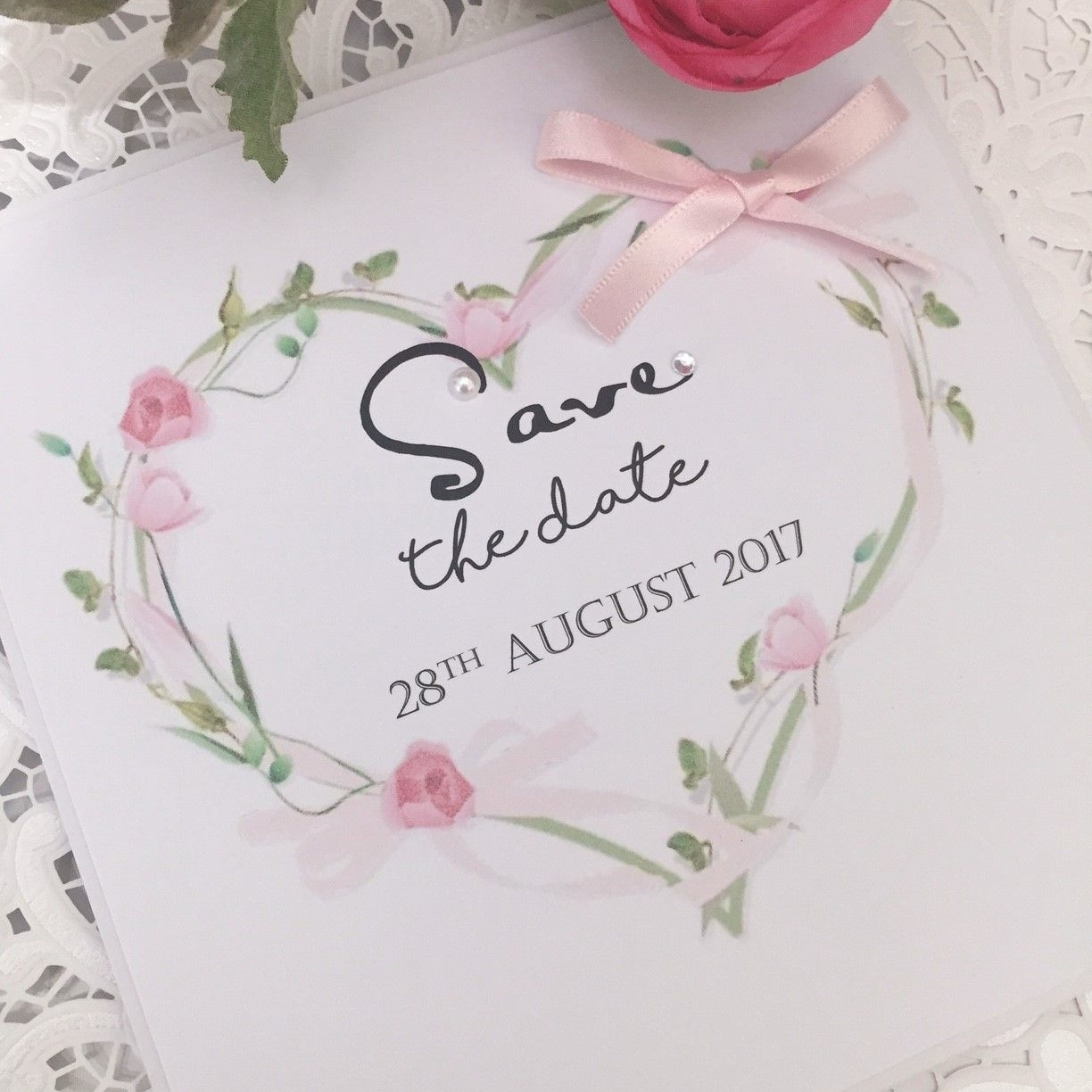 Save the date card with flower heart wreath and a pink bow
