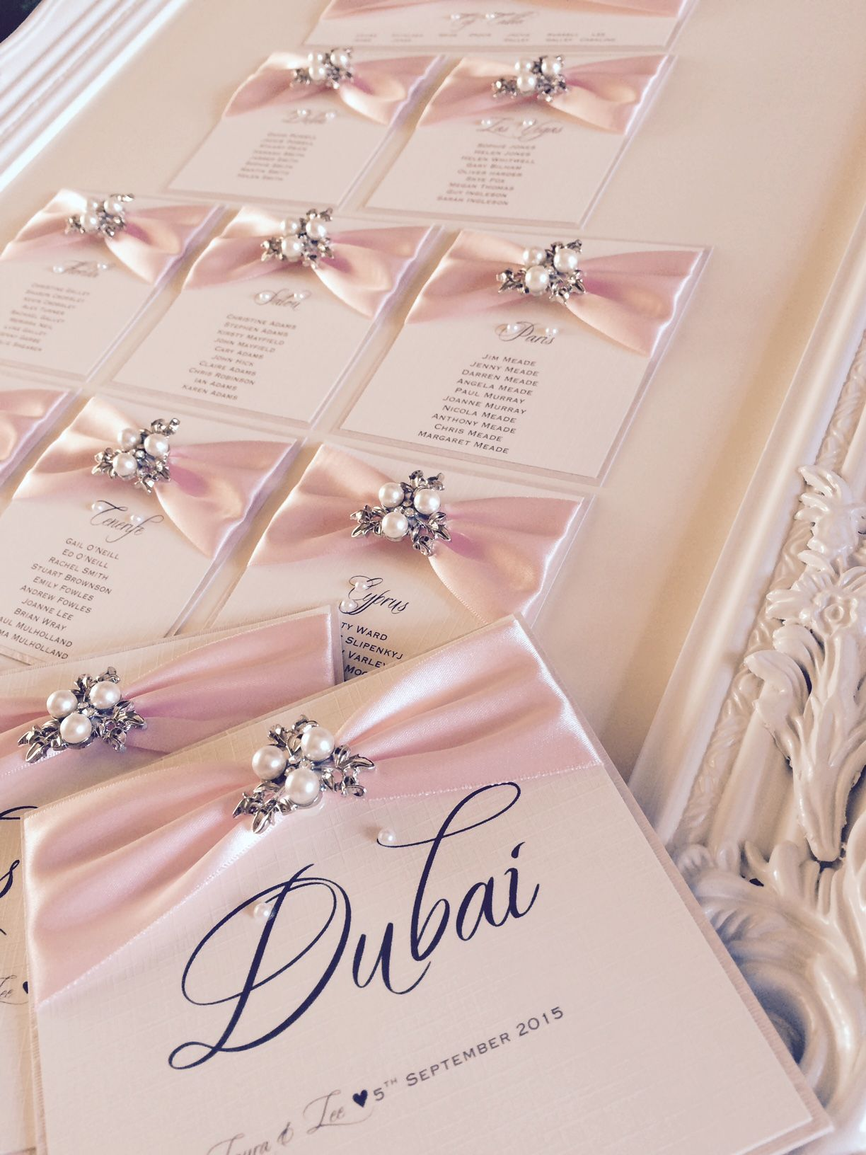 Elegant framed table plan with light pink ribbon and vintage brooches