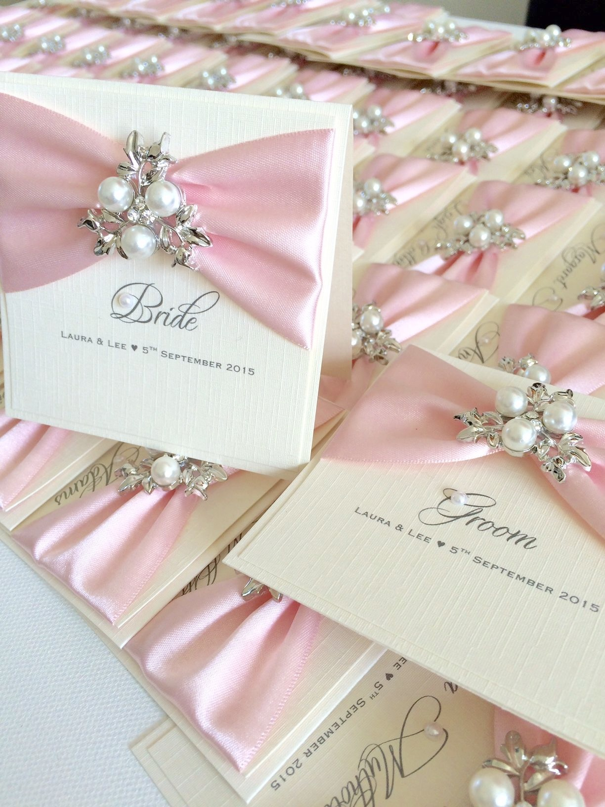 Beautiful place name cards with light pink ribbon and pearl brooch