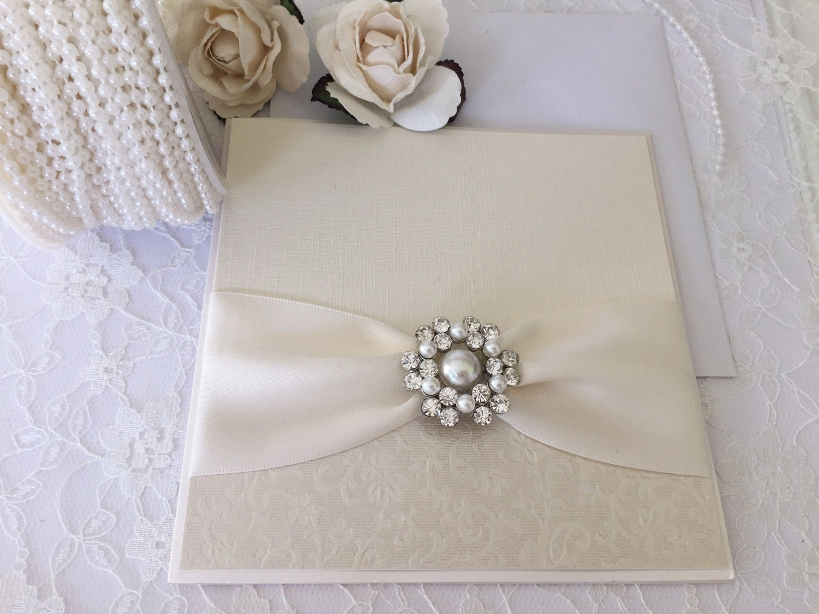 Vintage style invitations with pearl brooches