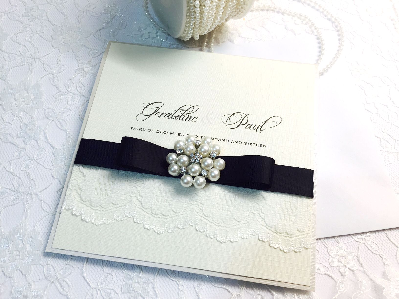 black and ivory invitation with dior bow and pearl