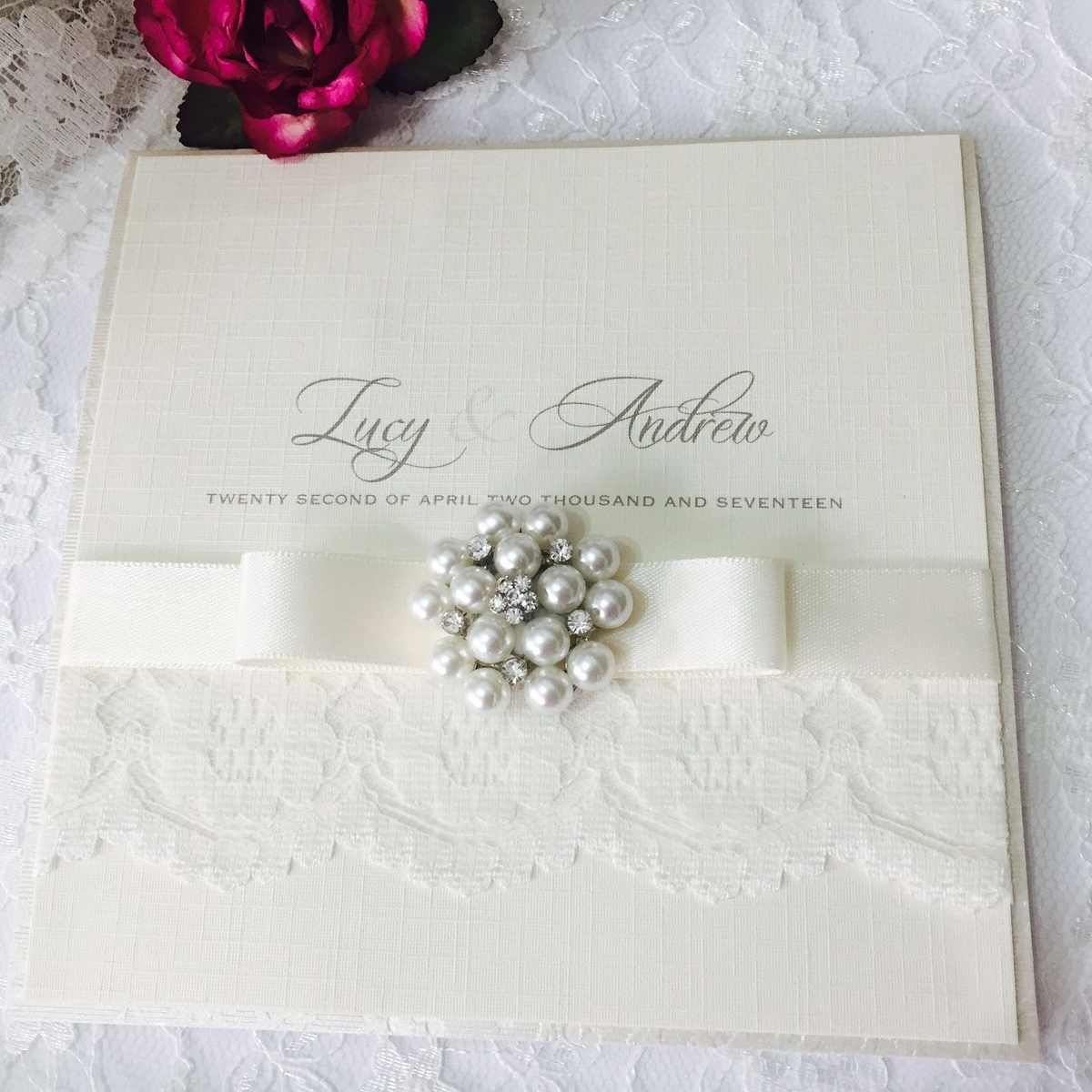 Ivory lace pocket fold invitation with bow and brooch in presentation box