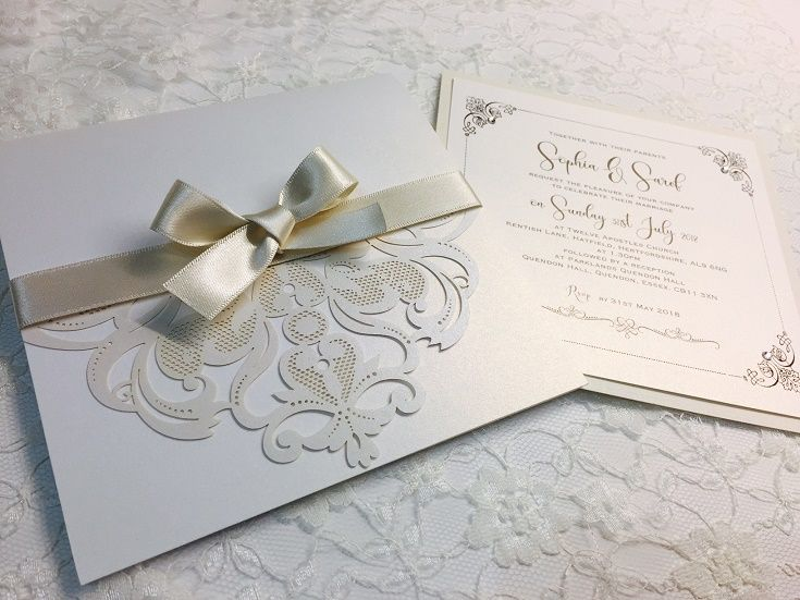 Laser cut pocket style invitations in champagne colour with ribbon bow