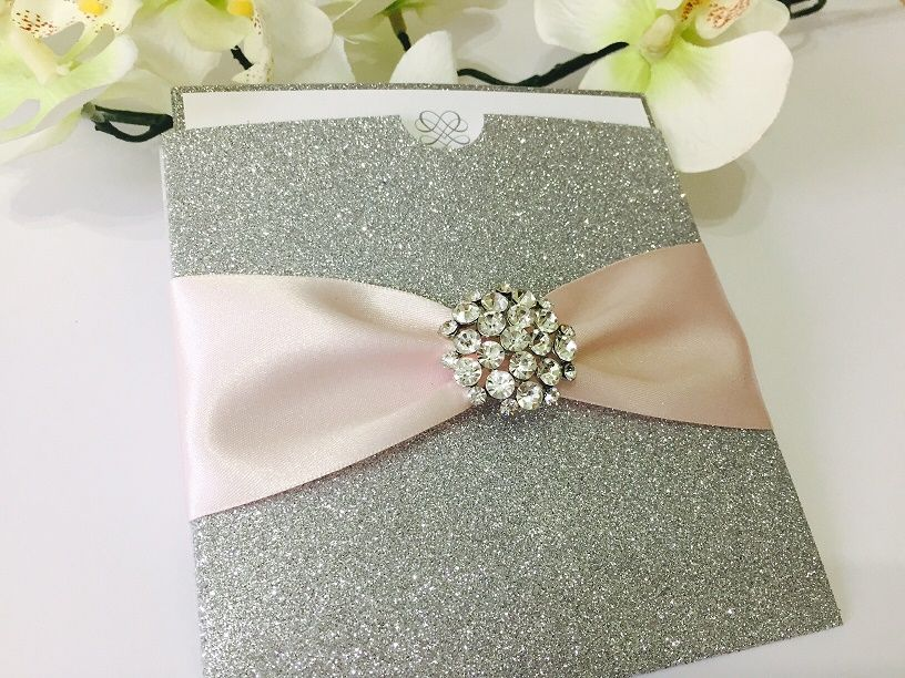Glitter pocket invitations in silver with diamante brooch