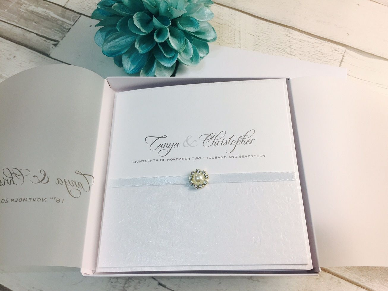 white wedding invitation in box with small pearl brooch
