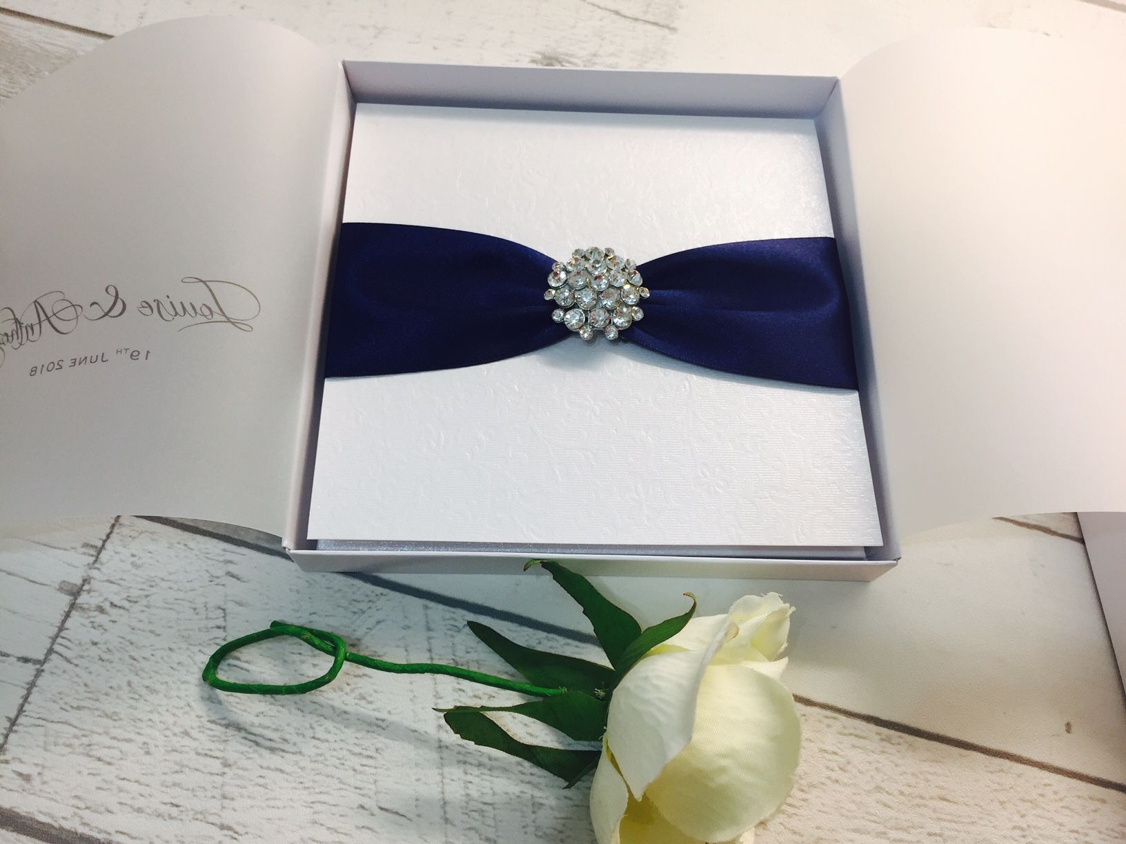 Luxury boxed wedding invitation with navy blue ribbon and diamante brooch