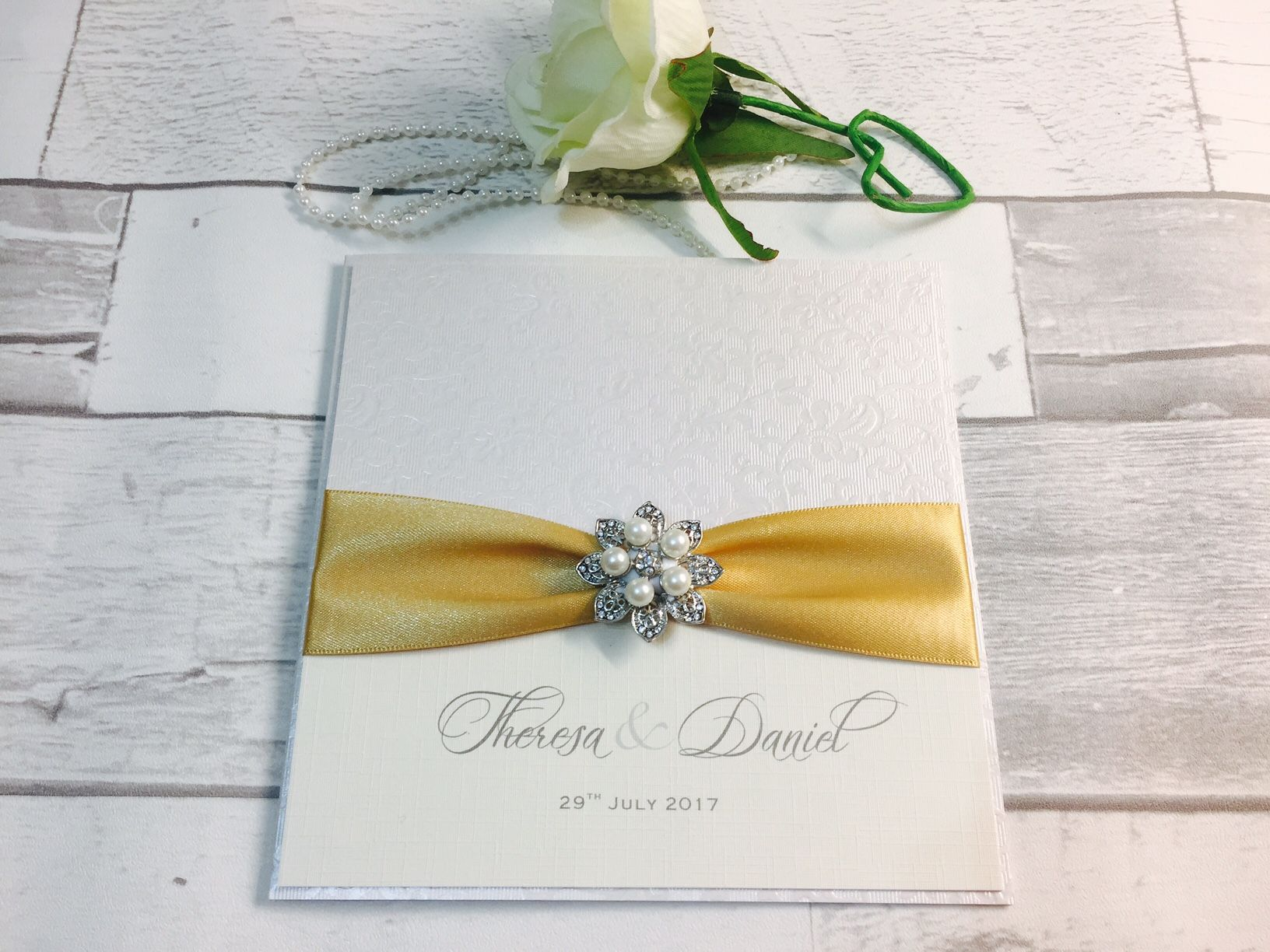 Pocket style vintage invitation with gold ribbon and pearl brooch