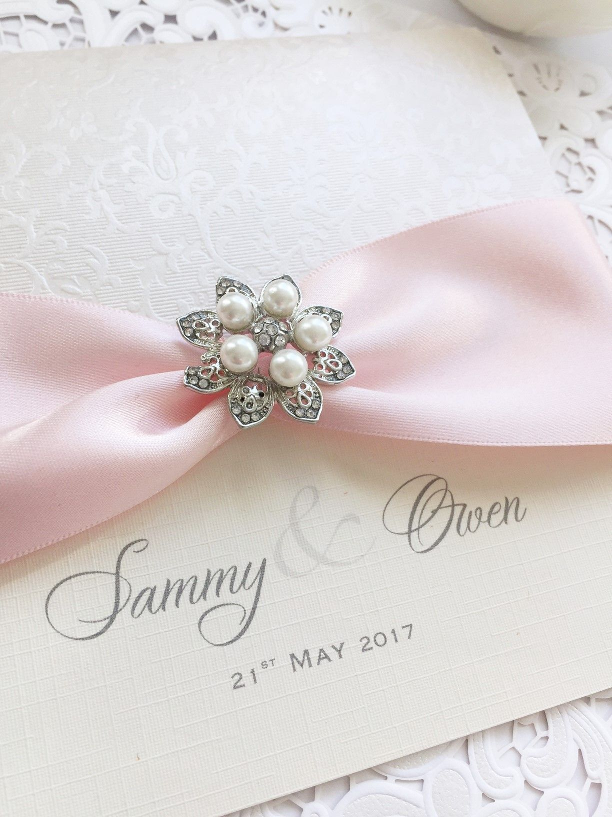 Pocket style luxury invitation with pink ribbon and pearl brooch