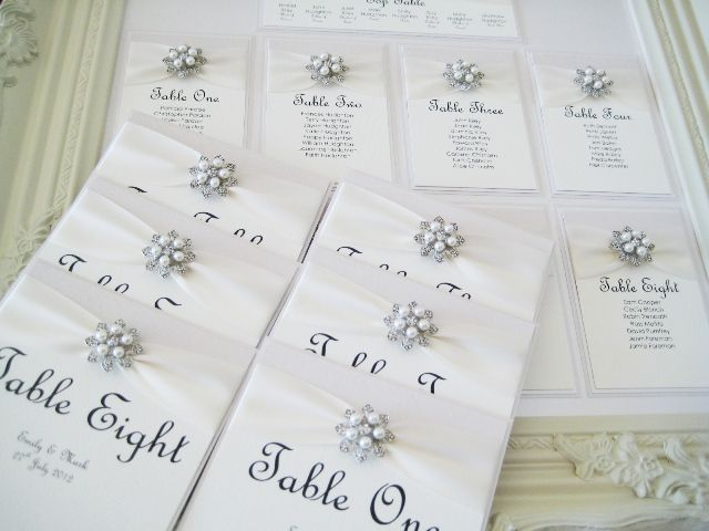 Framed seating plan with white ribbon and pearl brooch