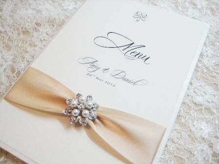 Personalised wedding breakfast menu with brooch and ribbon