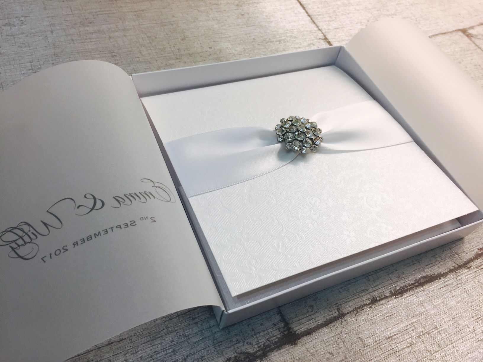 luxury boxed wedding invitation s with diamante brooch and white ribbon handmade in the UK